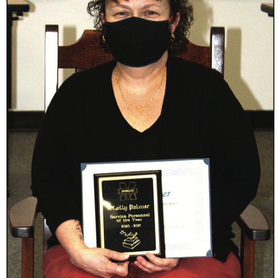 Holly Palmer was named Morgan County Schools Service Personnel of the Year at the March 30 Morgan County School Board meeting. The annual award recognizes outstanding education support personnel for their dedication, skill and contributions to their school and community. Palmer received a rocking chair from Caperton Furniture Works for her award. photo by Betsy Buser